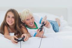 Hermanos alegres que juegan a los videojuegos Imagenes de archivo