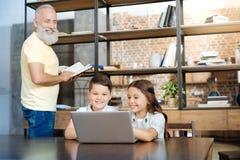 Hermanos alegres que miran los vídeos mientras que lectura de abuelo Fotografía de archivo libre de regalías
