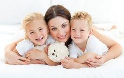 Hermanos Animated con su madre que miente en una cama Fotografía de archivo libre de regalías