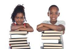 Hermanos apoyados en una pila de libros Foto de archivo libre de regalías