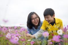 Hermanos asiáticos jovenes que tienen un rato de la diversión en el jardín Fotos de archivo libres de regalías