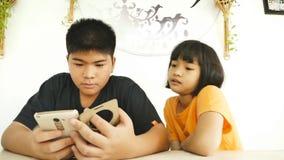 Hermanos asiáticos que usan el teléfono elegante almacen de metraje de vídeo