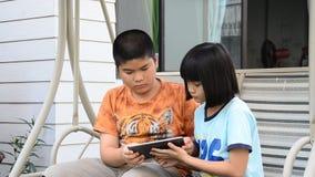 Hermanos asiáticos que usan la tableta metrajes