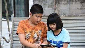 Hermanos asiáticos que usan la tableta almacen de metraje de vídeo