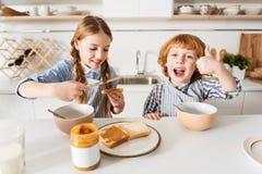 Hermanos brillantes brillantes que se divierten durante el desayuno Fotos de archivo libres de regalías