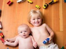 Hermanos cercados por un corazón hecho de los trenes y de los vehículos de madera imagenes de archivo