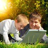 Hermanos con el ordenador portátil al aire libre Foto de archivo