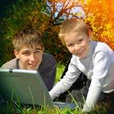 Hermanos con el ordenador portátil al aire libre Fotografía de archivo libre de regalías