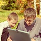 Hermanos con la computadora portátil Foto de archivo libre de regalías