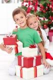 Hermanos con las porciones de presentes en el tiempo de la Navidad Foto de archivo libre de regalías