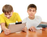 Hermanos con un libro y una tableta Foto de archivo