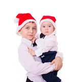 Hermanos de los muchachos en el abrazo de los sombreros de santa Imagen de archivo libre de regalías