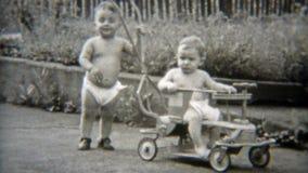 1949: Hermanos del bebé del gemelo fraternal que cuelgan hacia fuera en pañales NEWARK, NEW JERSEY almacen de metraje de vídeo