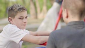 Hermanos del retrato dos que se sientan en el parque y la charla Muchachos de balanceo de la mujer en el fondo almacen de video