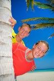 Hermanos detrás de la palmera Fotos de archivo