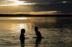 Hermanos en el agua de un lago en la puesta del sol Foto de archivo