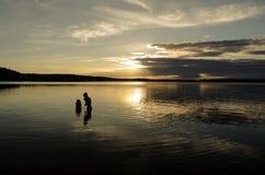 Hermanos en el agua de un lago grande en la puesta del sol Imagenes de archivo