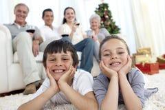 Hermanos en suelo con su familia en la Navidad fotografía de archivo libre de regalías