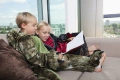Hermanos en trajes del dinosaurio y del vampiro que leen el libro ilustrado junto en sofá cama en casa Imágenes de archivo libres de regalías
