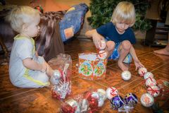 Hermanos en un proceso de adornar el árbol de navidad del Año Nuevo Fotos de archivo libres de regalías