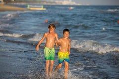 Hermanos felices funcionados con en la costa: Concepto de las vacaciones de verano Imágenes de archivo libres de regalías