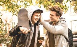 Hermanos felices jovenes que se divierten usando los teléfonos elegantes móviles Foto de archivo