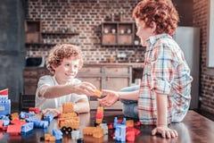 Hermanos felices positivos que juegan con el sistema del constructor Fotos de archivo