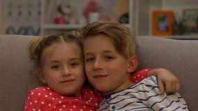 Hermanos felices que abrazan, sentándose en el sofá y mirando la cámara, unidad almacen de video