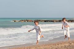 Hermanos felices que juegan en la playa, España Fotografía de archivo