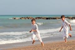 Hermanos felices que juegan en la playa, España Foto de archivo