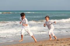 Hermanos felices que juegan en la playa, España Imagen de archivo libre de regalías