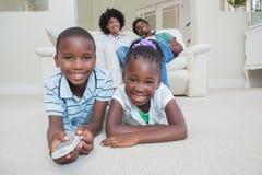 Hermanos felices que mienten en el piso que ve la TV foto de archivo libre de regalías