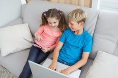Hermanos felices que usan la PC del ordenador portátil y de la tableta en el sofá Imagen de archivo libre de regalías