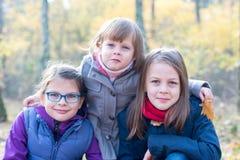 Hermanos felices - tres hermanas en la sonrisa otoñal del bosque Fotos de archivo libres de regalías