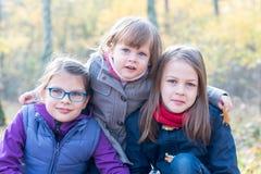 Hermanos felices - tres hermanas en la sonrisa otoñal del bosque Imagen de archivo