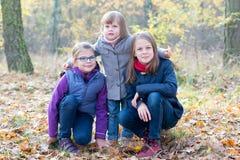 Hermanos felices - tres hermanas en la sonrisa otoñal del bosque Imagen de archivo libre de regalías