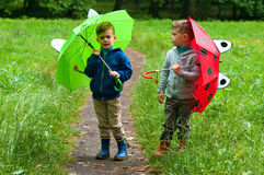 Hermanos gemelos con los paraguas Imágenes de archivo libres de regalías