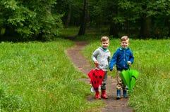 Hermanos gemelos con los paraguas Imagen de archivo libre de regalías