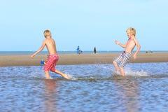 Hermanos gemelos que corren en la playa Foto de archivo libre de regalías