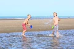 Hermanos gemelos que corren en la playa Fotografía de archivo libre de regalías