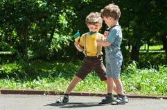 Hermanos gemelos que juegan con las piruletas a disposición Fotografía de archivo