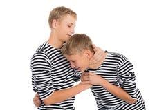 Hermanos gemelos que juegan una broma con uno a Imagen de archivo libre de regalías