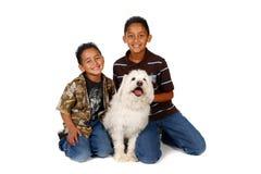 Hermanos hispánicos con su perro en blanco Imágenes de archivo libres de regalías