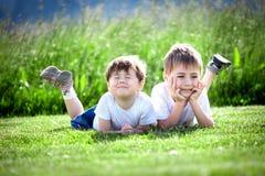 Hermanos jovenes en hierba Foto de archivo libre de regalías