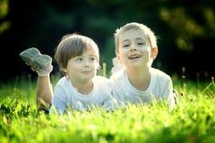 Hermanos jovenes en hierba Imágenes de archivo libres de regalías
