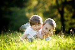 Hermanos jovenes en hierba Fotos de archivo libres de regalías