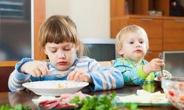 Hermanos junto que comen en la tabla de madera Fotografía de archivo libre de regalías