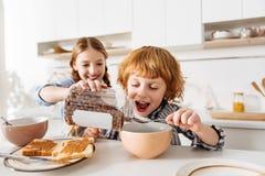 Hermanos lindos chistosos que engañan alrededor con la comida fotografía de archivo