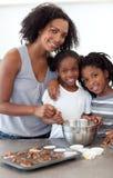 Hermanos lindos con su madre que hace las galletas Imagen de archivo libre de regalías