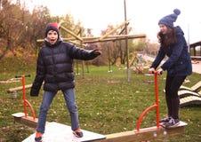 Hermanos muchacho y muchacha del adolescente en la ropa caliente que se divierte en parque del otoño Imágenes de archivo libres de regalías